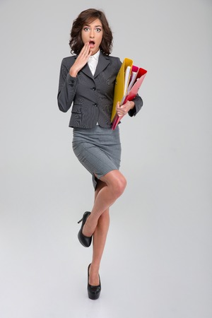 shoked: Shoked young curly pretty woman in gray costume standing on one leg in heel shoes and holding binders Stock Photo