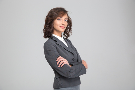 formalwear: Confident curly happy successful young woman in formalwear posing with crossed arms