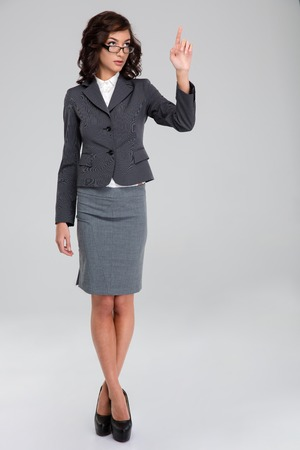 finger crossed: Confident curly pretty business woman in glasses and gray suit touching copyspace by finger and standing with crossed legs Stock Photo