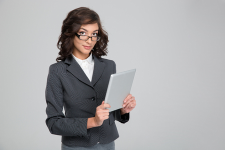 glases: Young beautiful curly business woman in gray jacket and glases using tablet