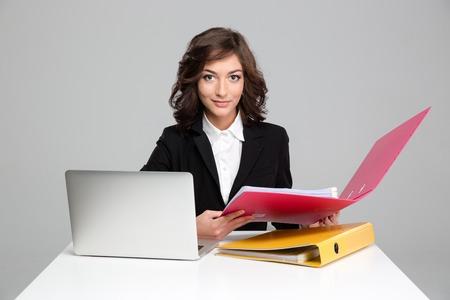 SECRETARIA: Joven secretaria confianza rizado de trabajo con ordenador y coloridos carpetas