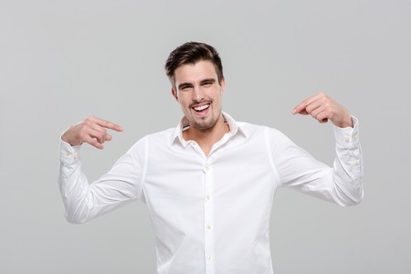 achievment: Smiling handsome successful happy confident man in white shirt pointing on himself Stock Photo