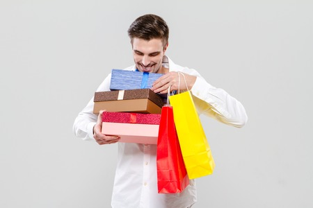 attractive charismatic: Handsome smiling happy young man in white shirt holding colorful gifts Stock Photo