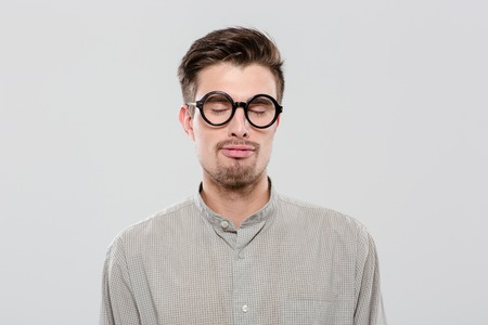 funny glasses: Young handsome funny amusing guy in gray shirt with closed eyes in black round glasses