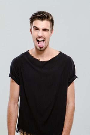 adults only: Young funny handsome guy in black t-shirt winking and sticking out his tongue