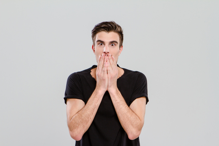 shoked: Emotional handsome young man in black t-shirt surprised and closed mouth with hands Stock Photo