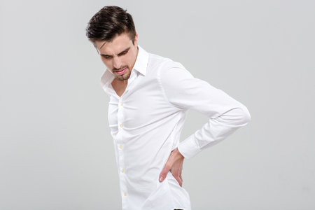 white shirt: Handsome attractive young man in white shirt has a backache Stock Photo