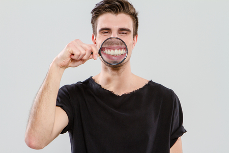 Young funny amusing guy having fun with magnifying glass