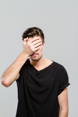adult only: Young handsome man doing facepalm covering his eyes and face with palm