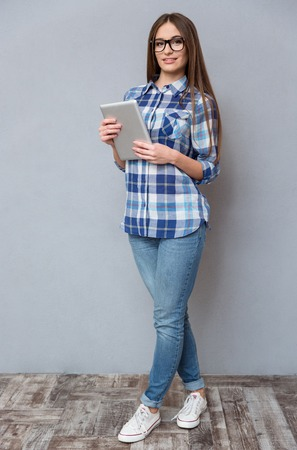 full lenght: Full lenght portrait of beautiful happy smiling smart girl in checkered shirt and glasses holding tablet