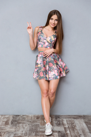 smiing: Beautiful young happy smiing positive stylish woman showing peace sign and smiling