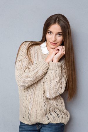 Portrait of young beautiful smiling girl with long hair in knitted beige sweater