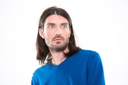 long depression: Young handsome man with long hair in blue sweetshirt looking surprised