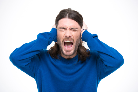 young adult man: Desperate hysterical angry man with long hair closed ears by hands and screaming with opened mouth