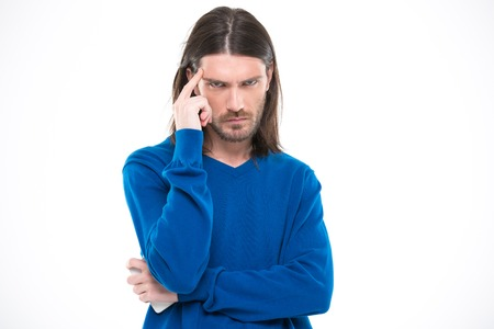 unkind: Angry mad man with long hair in blue pullover touching his temple