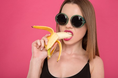 Closeup of young seductive attractive sensual model in black sunglasses eating banana on pink background Zdjęcie Seryjne