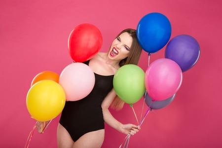 turnanzug: Verr�ckte ausgeflippt bizarr schreit junge Frau im schwarzen Anzug pozing mit bunten Luftballons auf rosa Hintergrund