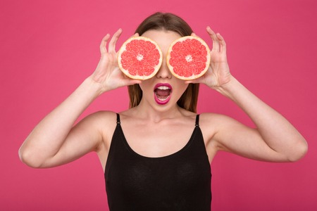 Joyful female with two half of tasty juicy grapefruit instead eyes Stock Photo