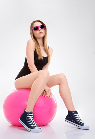 fitball: Beautiful attractive confident relaxed young woman in black leotard and pink sunglasses posing on pink fitball Stock Photo