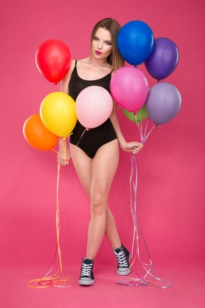 turnanzug: Beautiful seductive attractive young lady in black leotard and sneakers posing with colorful balloons on pink background