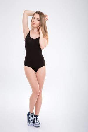 turnanzug: Verführerische sinnlich natürlich hübsche junge Frau in schwarzen Anzug posiert auf weißem Hintergrund