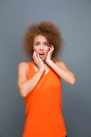 wondered: Portrait of scared shocked afraid frightened curly girl in orange top on gray background Stock Photo
