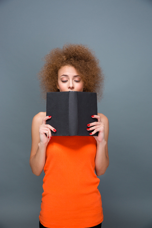 voluminous: Concentrated calm attractive girl in orange top with voluminous curly hairstyle reading an interesting book Stock Photo