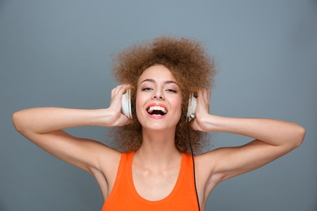lovely women: Happy cheerful beautiful  laughing curly girl listening music using headphones Stock Photo