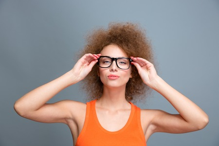 voluminous: Portrait of confident young beautiful concentrated female with voluminous curly hairstyle in black glasses