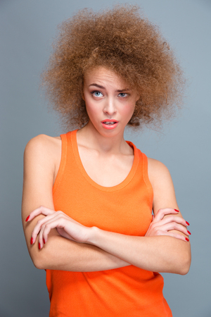 wondered: Beautiful curly wondered amazed surprised young woman in orange top shocked and posing with crossed arms on gray background