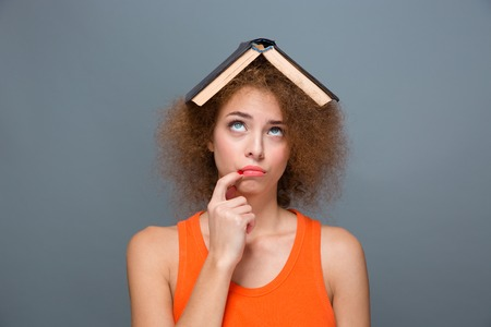 forefinger: Portrait of curly annoyed bored tired young woman in orange top looking funny with book on head touching lips with forefinger and looking up