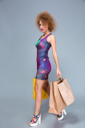 paperbags: Concentrated beautiful attractive gorgeous curly woman in colorful dress and platform summer shoes walking with paperbags after shopping