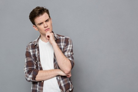 pensive: Young serious smart concentrated pensive guy in plaid shirt holding hand on his chin Stock Photo