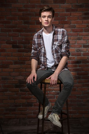 bar chair: Confident handsome pensive modern young guy in plaid shirt sitting on bar chair Stock Photo