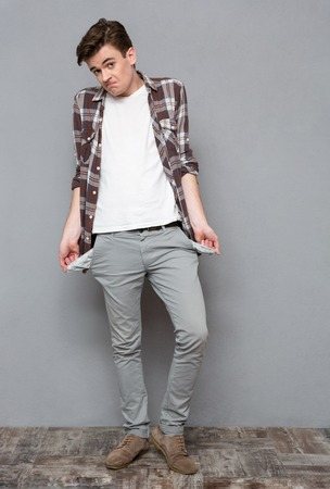 exhibiting: Full length portrait of a casual man exhibiting his empty pockets on gray bakground