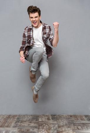 persona saltando: Hombre positivo cheerfu encantados despreocupado joven en camisa a cuadros y pantalones grises que salta en el aire y la sonrisa