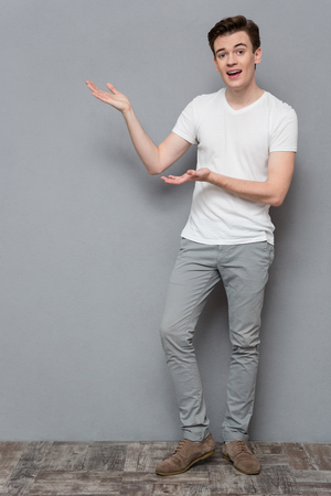 copyspace: Full length portrait of attractive inspired happy smiling casual young man in white t-shirt and gray pants holding copyspace on palms over gray background Stock Photo