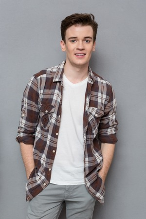 attractive charismatic: Portrait of handsome young happy positive man in checkered shirt  posing and smiling on gray background