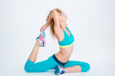 happy people: Portrait of a sports woman doing stretching exercises isolated on a white background Stock Photo