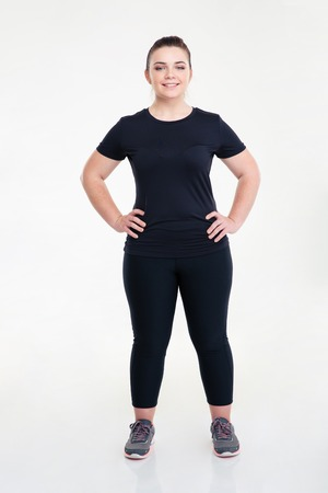 girl in sportswear: Portrait of a happy fat sports woman standing isolated on a white background Stock Photo