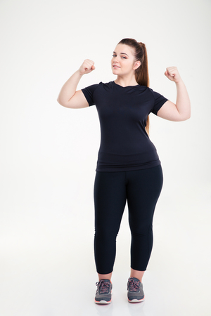 Full length portrait of a happy fat woman showing her biceps isolated on a white background