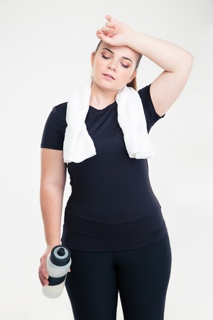 tired woman: Portrait of a tired fat woman in sports wear standing isolated on a white background