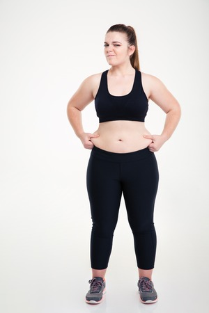 fat belly: Full length portrait of a woman pinches fat on her belly isolated on a white background
