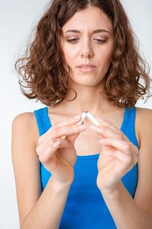 braking: Portrait of a beautiful woman braking cigarette isolated on a white background Stock Photo