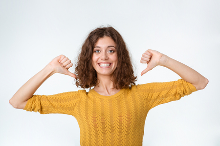 egocentric: Portrait of a funny smiling woman pointing fingers on herself isolated on a white background