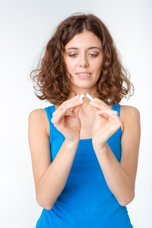 braking: Portrait of a young woman braking cigarette isolated on a white background