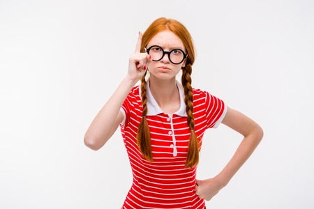 wag: Strict young redhead woman with two braids in round glassees pointing up isolated on white background