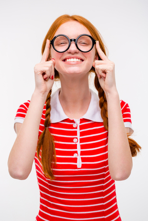 pleased: Cheerful pleased funny young female with two braids fixing round glasses and smiling isolated over white background