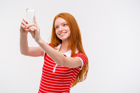 pretty: Portrait of a cheerful young pretty woman with beautiful long red hair making selfie using cellphone over white background