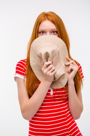 embarrassed: Embarrassed shy redhead young woman hiding her face behind hat posing on white background